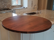 "Walnut flat grain wood countertop, 48"" diameter circle , ¼"" roundover edge, permanent finish. Designed by Arcadia Homes. Installed in Concord, North Carolina."